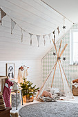 Wigwam in child's bedroom with sloping ceiling