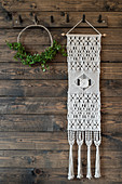 Macrame wall hanging and minimalist wreath on board wall