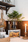 Lit candles in front of box of pastries and small Christmas tree