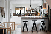 Barstools at counter in industrial-style kitchen