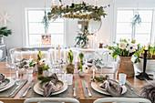 Weihnachtlich gedeckter Tisch unterm hängenden Adventskranz