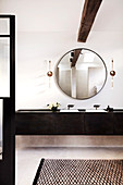 Bathroom with round wall mirror and double vanity made of dark wood