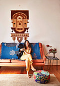Young woman with dog sits on sofa with blanket, ethnic wall hanging above