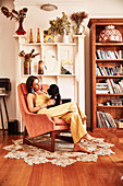 Young woman sits with dog in armchair in front of fireplace shelf