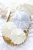 White paper stars and snowflakes on golden tray
