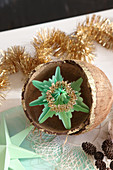 Star made from folded green paper in gilded coconut shells