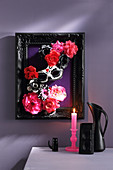 3D diorama of fabric flowers and mask in black picture frame on wall