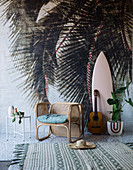 Rattan armchair and surfboard against a palm tree wall