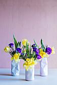 Frühlingsblumen in drei Vasen in Form zerdrückter Dosen