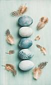 Blau gefärbte Ostereier aufgereiht mit Federn auf hellblauem Untergrund