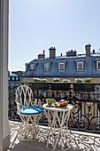 Tisch und Stuhl auf dem sonnigen Balkon in Paris