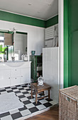 Open-plan bathroom with chequered floor and green accents