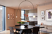 Designer lamps above dining table with open-plan kitchen in background