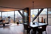 Moderner Wohnraum mit Fensterfront und Stadtpanorama