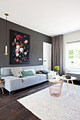 Grey sofa with scatter cushions below floral painting in living room