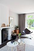Beistelltische, Kamin und Designerstuhl im Wohnzimmer