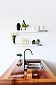 Island counter with wooden worksurface and sink in white kitchen