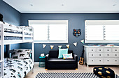 Bunk beds, couch and white chest of drawers in room with blue walls