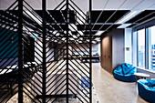 Blick durch Raumteiler in Lounge mit blauen Sitzsäcken vor Fenster