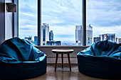 Two blue beanbags and side table next to window