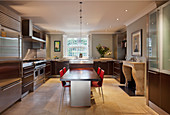 Dining table, red chairs and open fireplace in large modern kitchen
