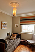 Modern lamp hung from stucco rosette above single bed