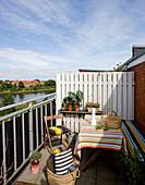 Tisch, Sitzmöbel und Kissen im Streifen-Look auf Balkon