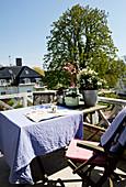Tisch mit lila Tischdecke und Stühle auf Balkon