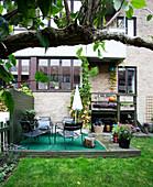 Grüner Teppich und Sitzmöbel auf Holzpodest im Garten