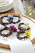 Wicker wreaths decorated with spring flowers to be used as napkin rings