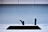 Black sink and taps in front of herringbone-patterned splashback