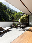 Open folding doors leading onto sunny terrace with seating area