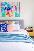 Colorful painting over the bed with lots of different pillows