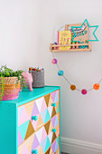 Chest of drawers painted with pastel colored triangle pattern in children's room