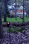 Blick auf beleuchtete Villa im Wald