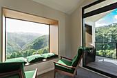 Grüne Polstersessel und passende Kissen auf Fensterbank vor Panoramafenster mit Landschaftsblick