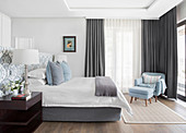 Elegant bedroom in pale blue, white and grey with ensuite bathroom