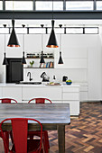 Wooden dining table with red chairs in front of white fitted kitchen