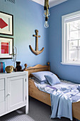 Maritime children's room with light blue wall and anchor