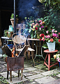 Brazier in front of vases of flowers on garden table
