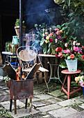 Feuerkorb vor Gartentischen mit Blumensträußen