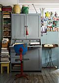 Alter Stuhl vor einem grauen Sekretär im Vintage-Wohnraum