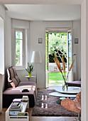 Modernes Wohnzimmer mit Gartenzugang und schräger Ecke