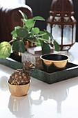 Deko-Ananas in goldener Schale vor einem Tablett mit Glückstaler