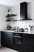 Modern, black fitted kitchen with white worksurface