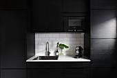 Moderne schwarze Einbauküche mit weißer Arbeitsplatte in der Nische