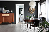Eclectic mixture of styles in dining room with black walls