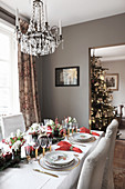 Festively set dining table and Christmas tree visible in open doorway