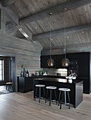 Modern, open-plan kitchen with black cabinets in grey log cabin