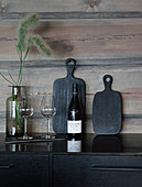 Black chopping boards, bottle of wine and glasses against wooden wall